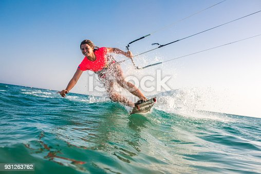 Woman doing kitesurfing on sea and smiling.