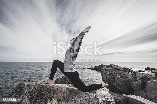 Young woman doing a low lunge or Anjaneyasana yoga pose at the sea