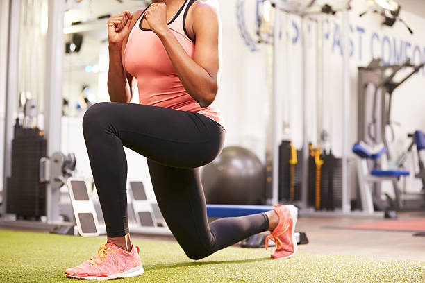 woman doing lunges in a gym, crop - lunge stock photos and pictures