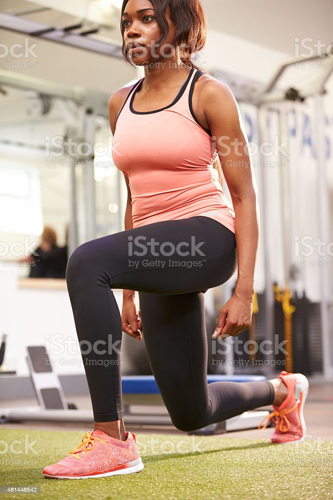 Woman doing lunges in a gym, vertical stock photo