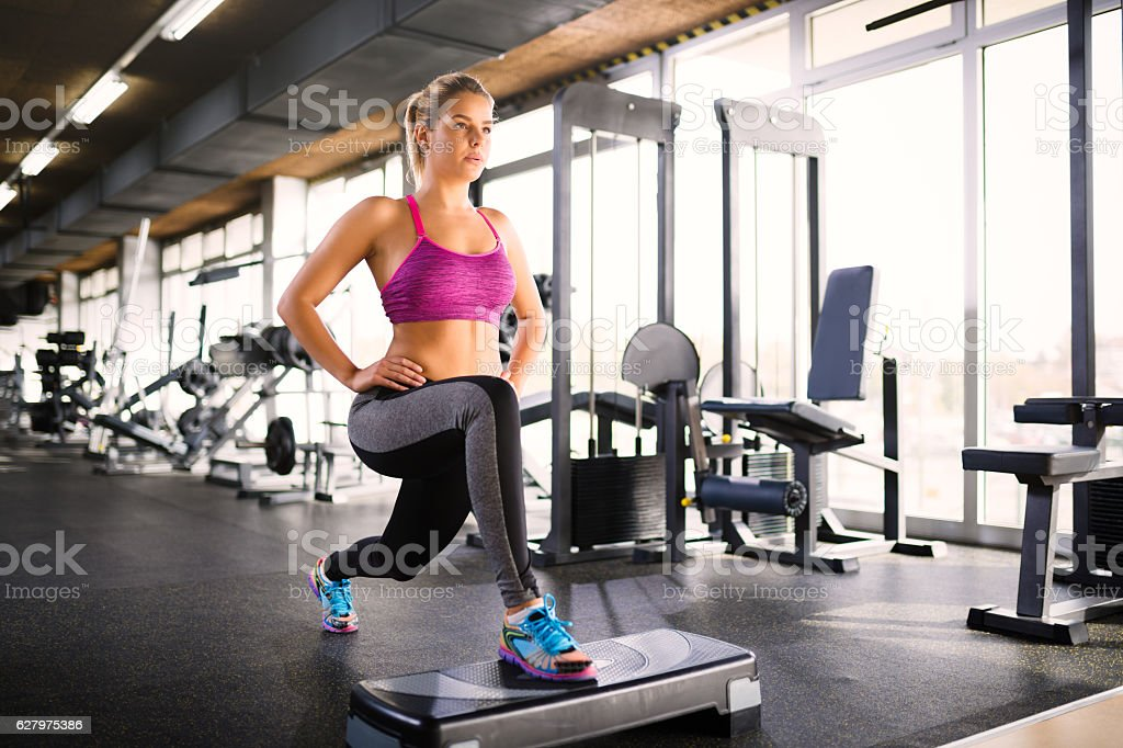 Woman doing lunges on step aerobics equipment at gym. stock photo