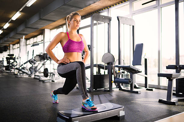 woman doing lunges on step aerobics equipment at gym. - lunge stock photos and pictures