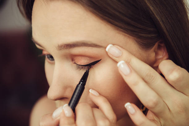 Woman doing makeup and painting black arrows stock photo