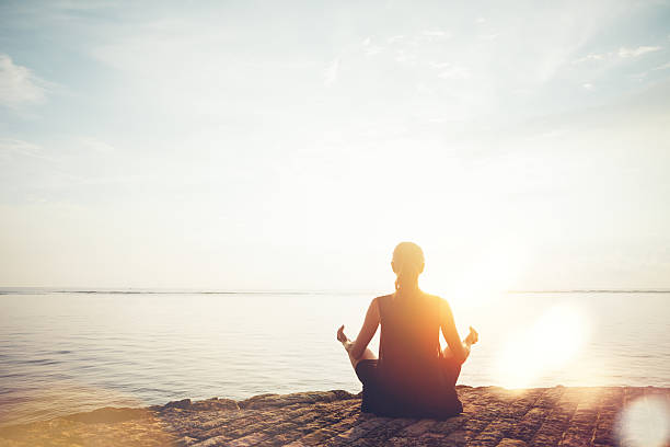 Woman doing meditation practice on the beach stock photo