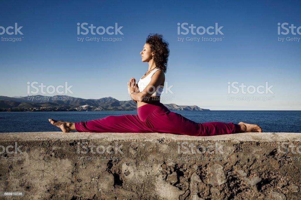 Woman doing monkey yoga pose stock photo