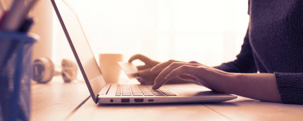 Woman doing online shopping using her laptop and a credit card, hands close up, e-commerce and online banking concept stock photo