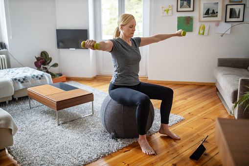 Woman sitting on a fitness ball in living room and working out with dumbbells. Woman is doing online exercise with digital tablet in front during self isolation at her living room.