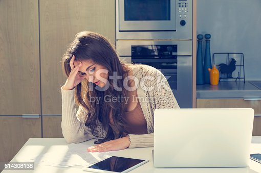 istock Woman doing paperwork with a laptop and digital tablet. 614308138