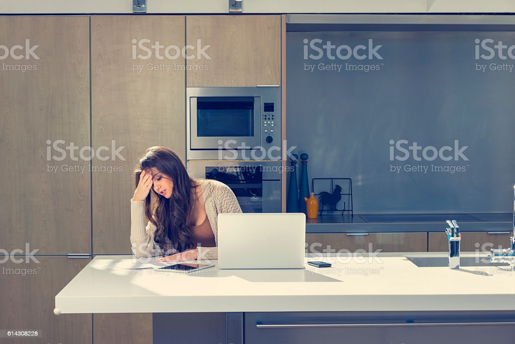 Woman doing paperwork with a laptop and digital tablet. stock photo