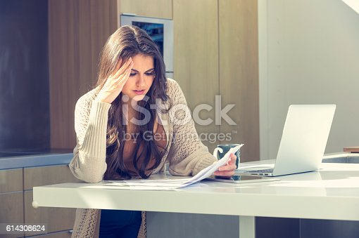 istock Woman doing paperwork with a laptop and digital tablet. 614308624