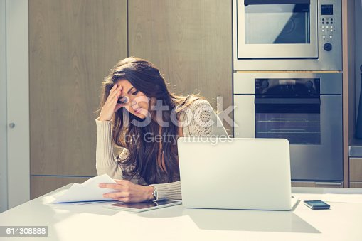 istock Woman doing paperwork with a laptop and digital tablet. 614308688