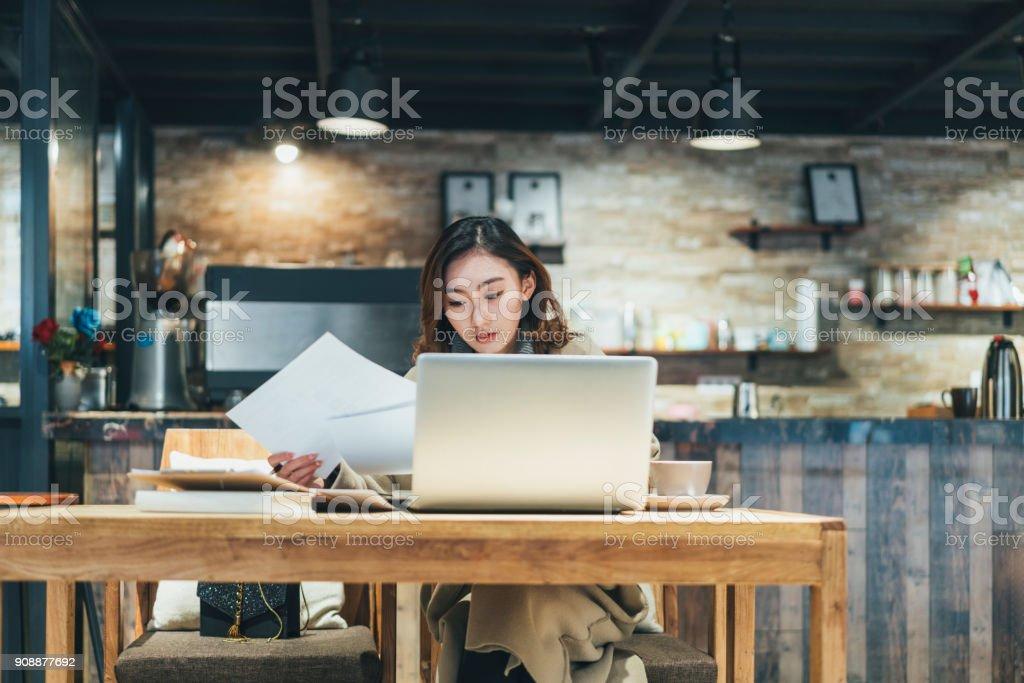 mujer haciendo papeleo con laptop en cafetería - foto de stock
