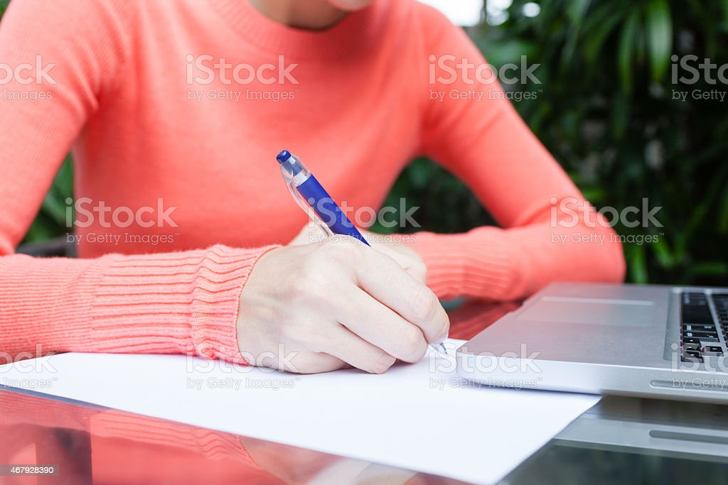 Woman doing paperwork with pen stock photo