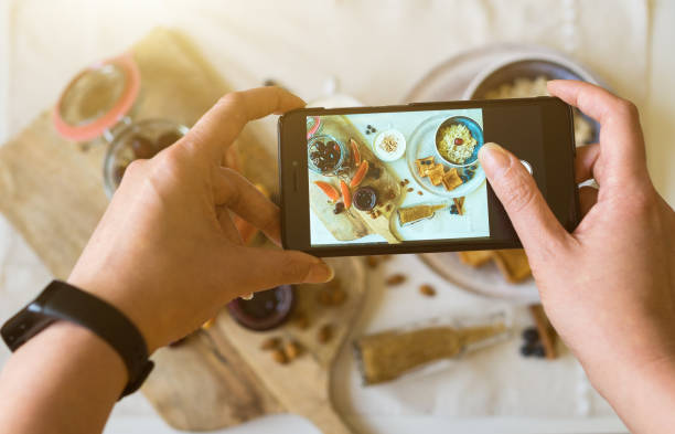 Woman doing photo of morning breakfast on mobile phone. stock photo