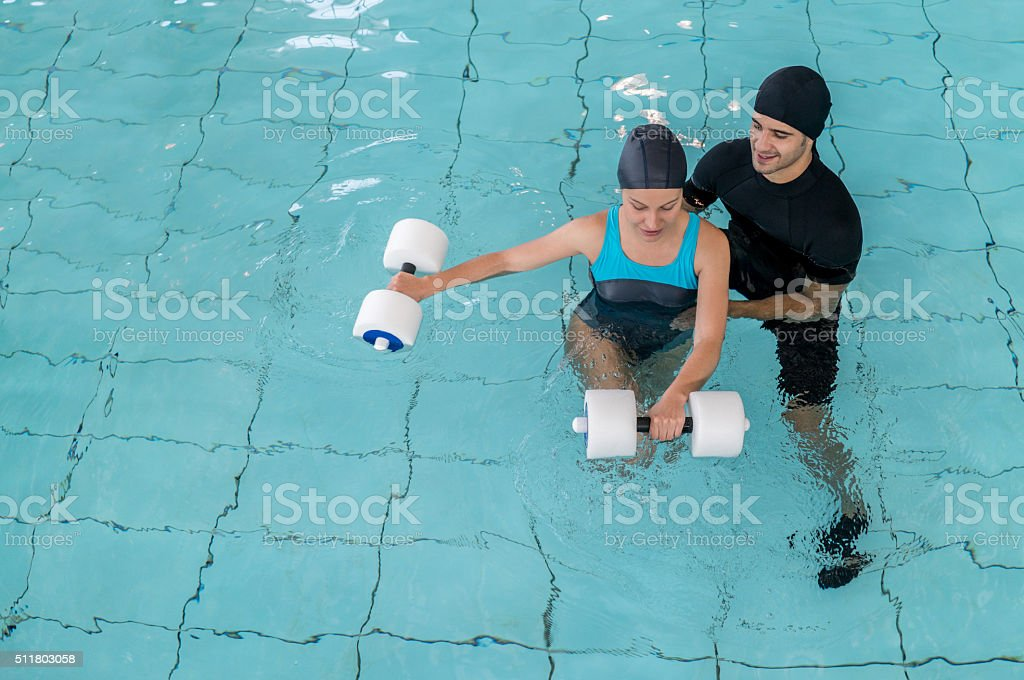 Woman doing physical therapy in the swimming pool stock photo