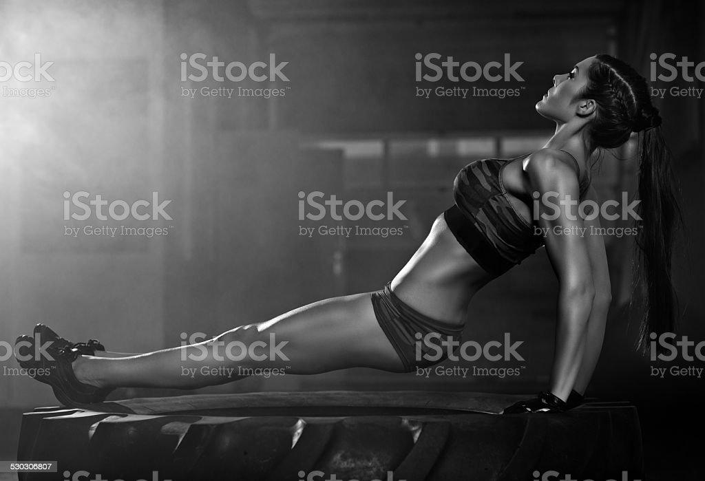 woman doing press ups on wheel stock photo