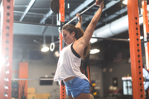 istock Woman doing pull ups during a cross training workout 598078210