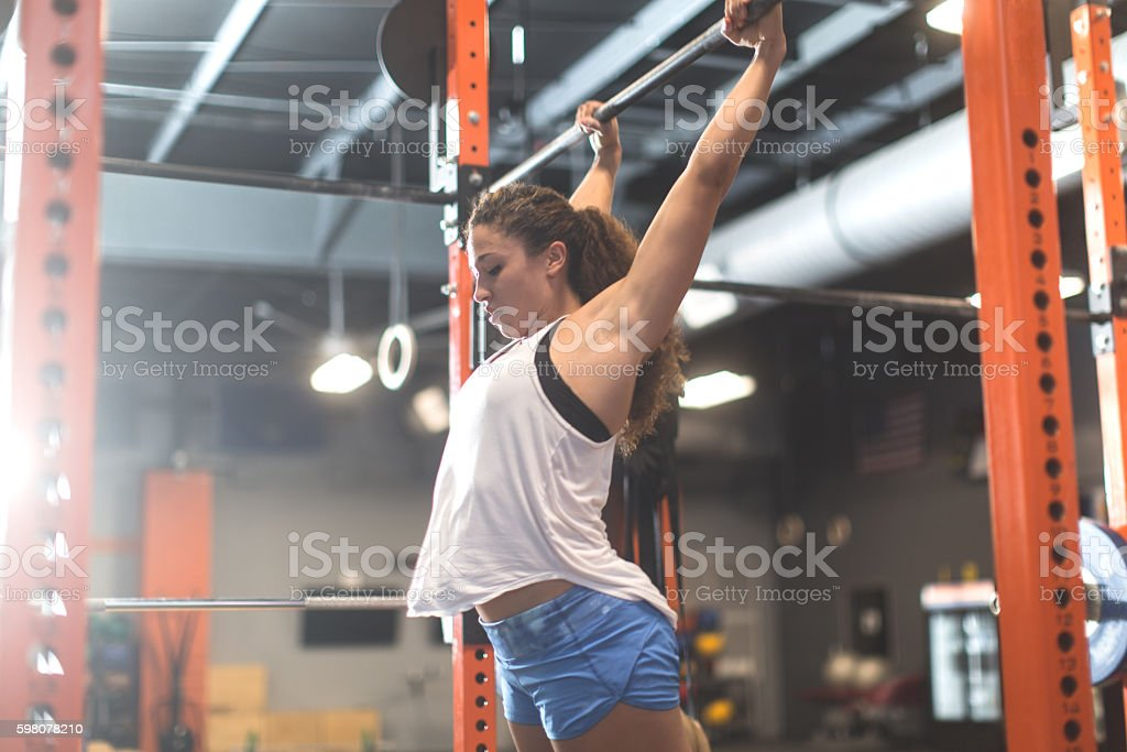 Woman doing pull ups during a cross training workout stock photo
