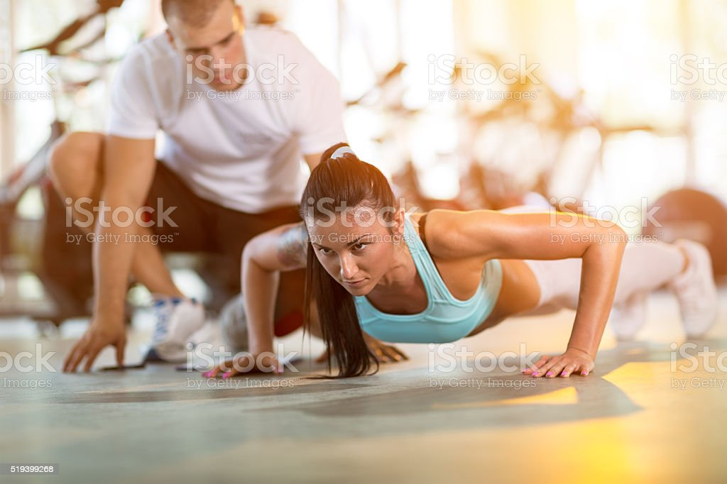 woman doing push ups under supervision of a trainer stock photo