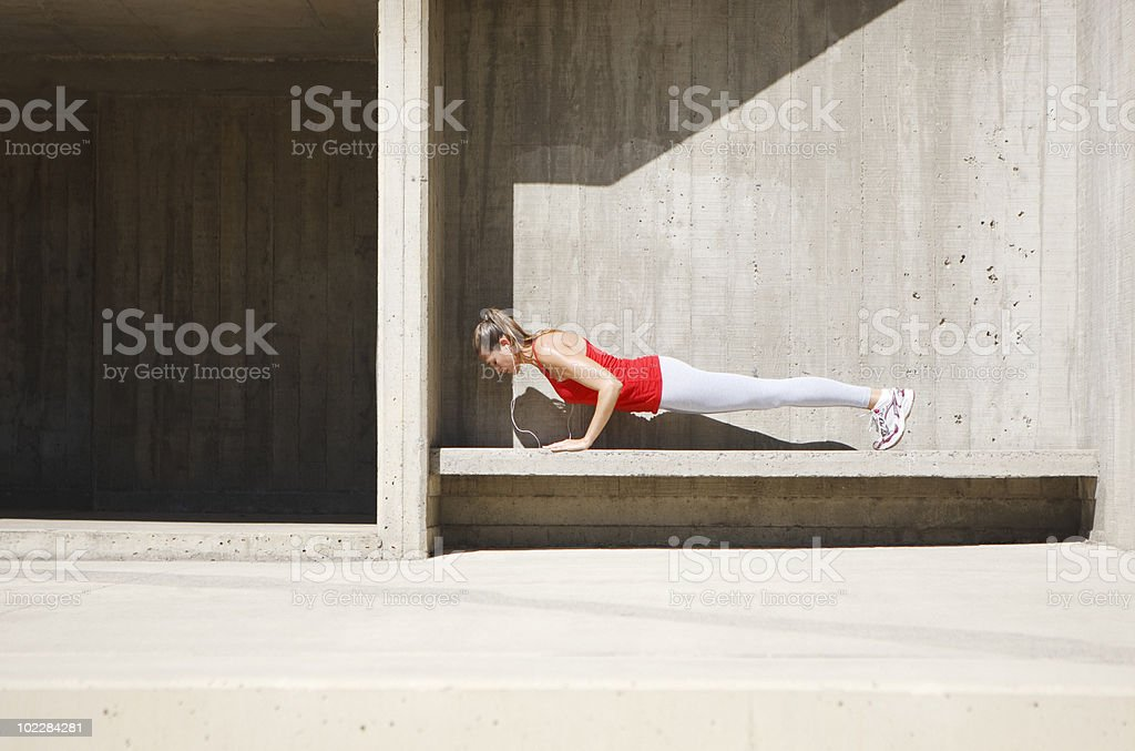 Woman doing push-ups on concrete bench royalty-free stock photo