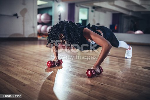 One woman, doing push-ups on dumbbells in gym.