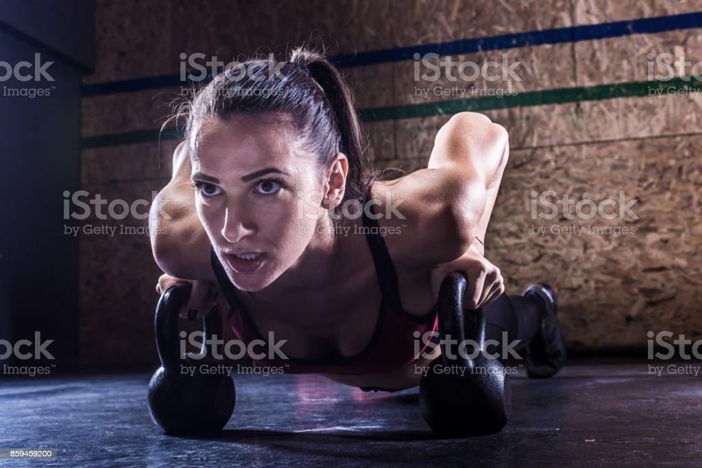 woman doing pushups on kettlebells stock photo