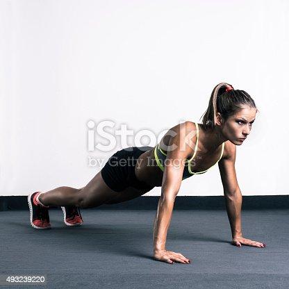 629605142istockphoto Woman doing push-ups 493239220