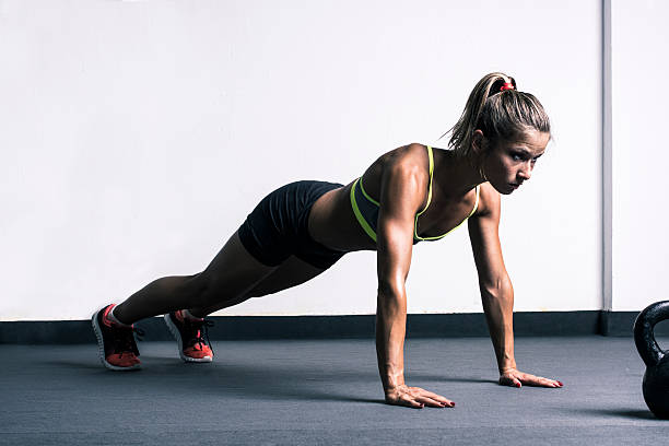 Woman doing push-ups Woman doing push-ups in gym tuff stock pictures, royalty-free photos & images