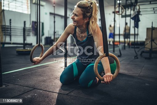 Young muscular woman exercising on gymnastic rings