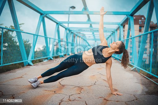 Young woman doing side plank pose on bridge