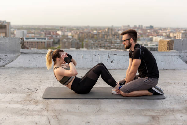 woman doing sit ups - man city exercise abs foto e immagini stock
