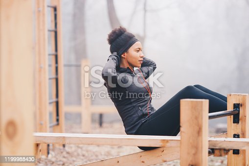 A woman doing sit-ups outdoors on an outdoor fitness equipment. She is wearing headphones, sweatshirt and leggings. She has a headband and a hair-bun. It's a foggy day.