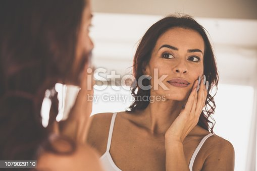 istock Woman doing skin care routine at home 1079029110