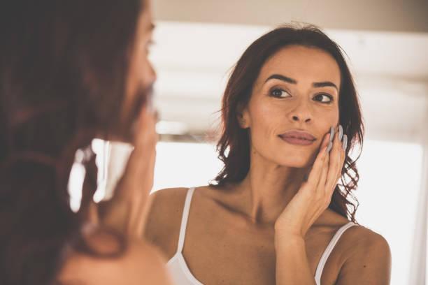 vrouw huidverzorging routine thuis doen - mid volwassen vrouw stockfoto's en -beelden