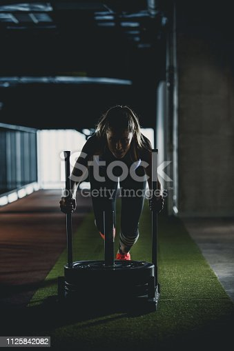 Front view of an athletic woman pushing weighted sled in a dark gym.