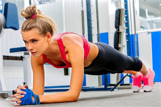 frau tun, push-ups im fitnessstudio zu - taillentrainer stock-fotos und bilder