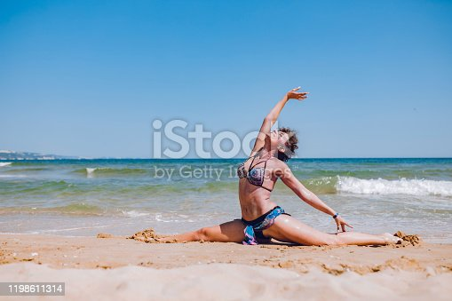 Young woman with face and body paint doing split on the beach.