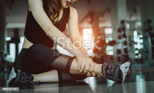 istock Woman doing sport exercise injury leg accident at gym fitness 886560952