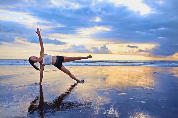 Woman doing sport exercise on sunset beach stock photo