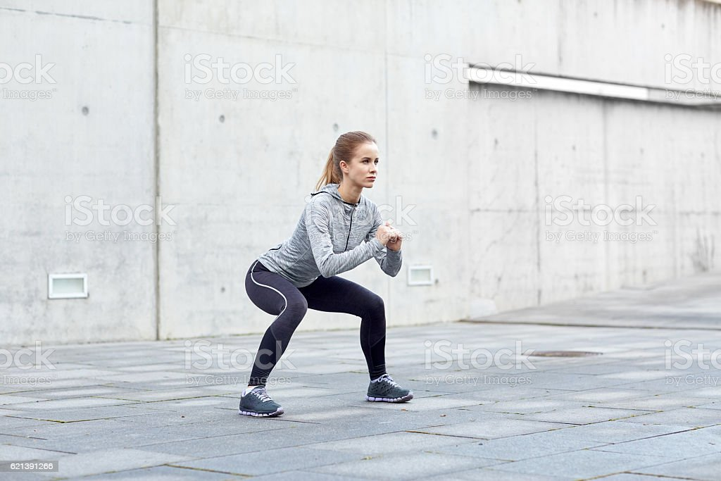 woman doing squats and exercising outdoors - foto de stock