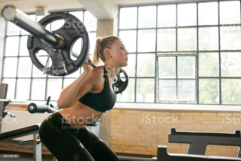 Woman doing squats in fitness club stock photo