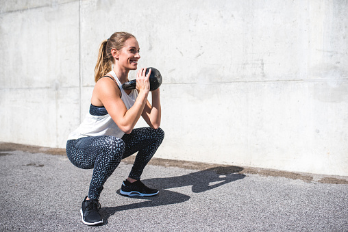 istock Woman doing squats with a kettlebell 879709092