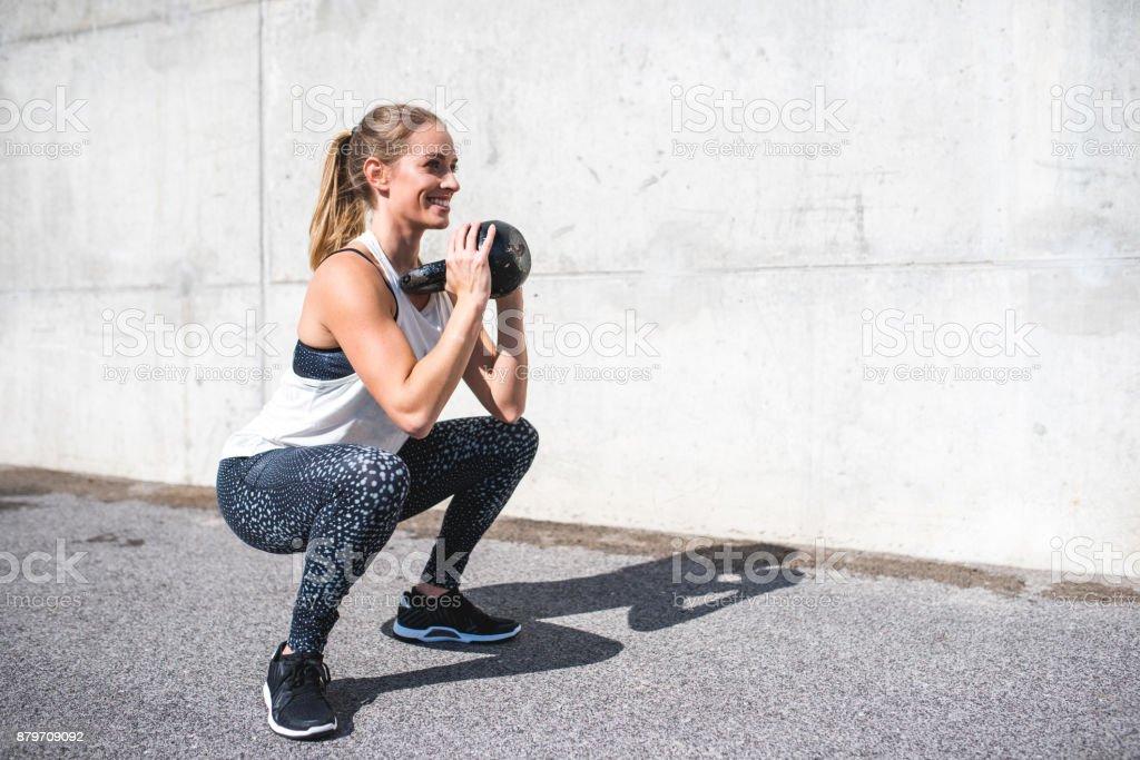 Mulher fazendo agachamentos com um kettlebell - foto de acervo