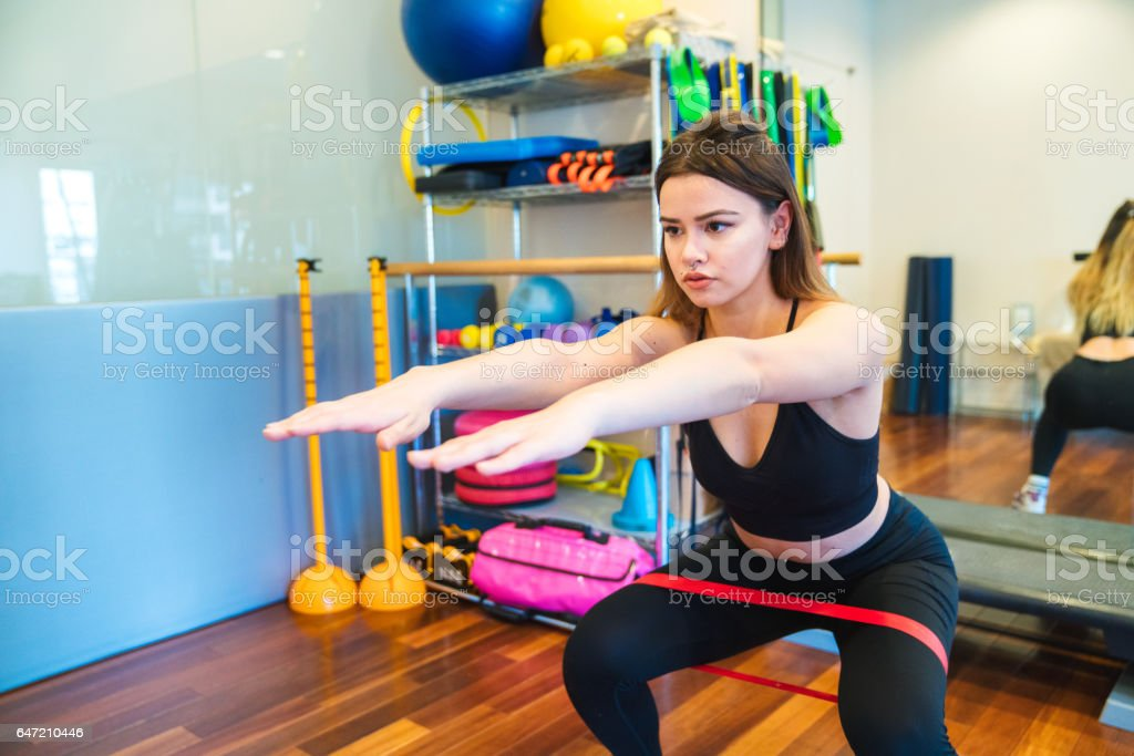 Woman doing squats with loop resistance band stock photo