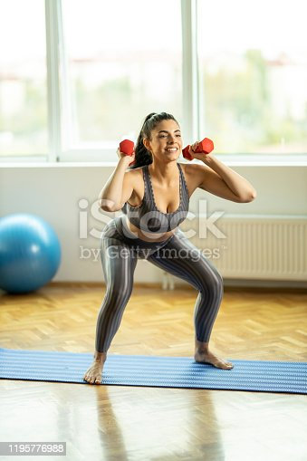 1035512048istockphoto Woman doing squats with weights 1195776988