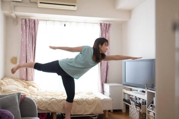朝のベッドでストレッチをしている女性 - 独身の若者 ストックフォトと画像