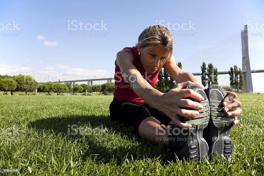 A woman doing stretches while sitting on grass royalty-free stock photo