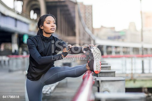 Determined woman doing stretching exercise by railing. Confident female athlete is warming up. She is looking away.