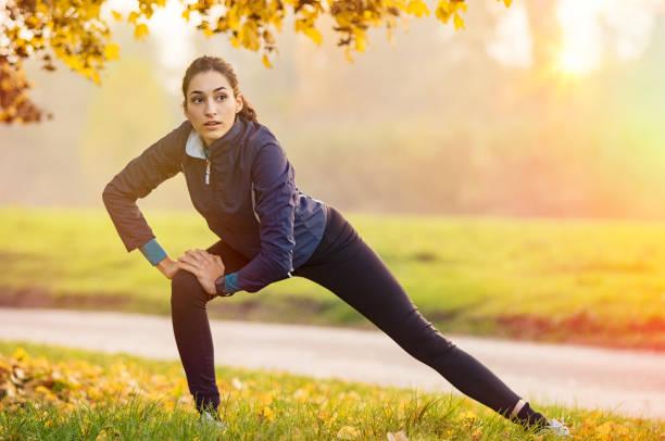 frau tun stretching-übung - joggerin stock-fotos und bilder