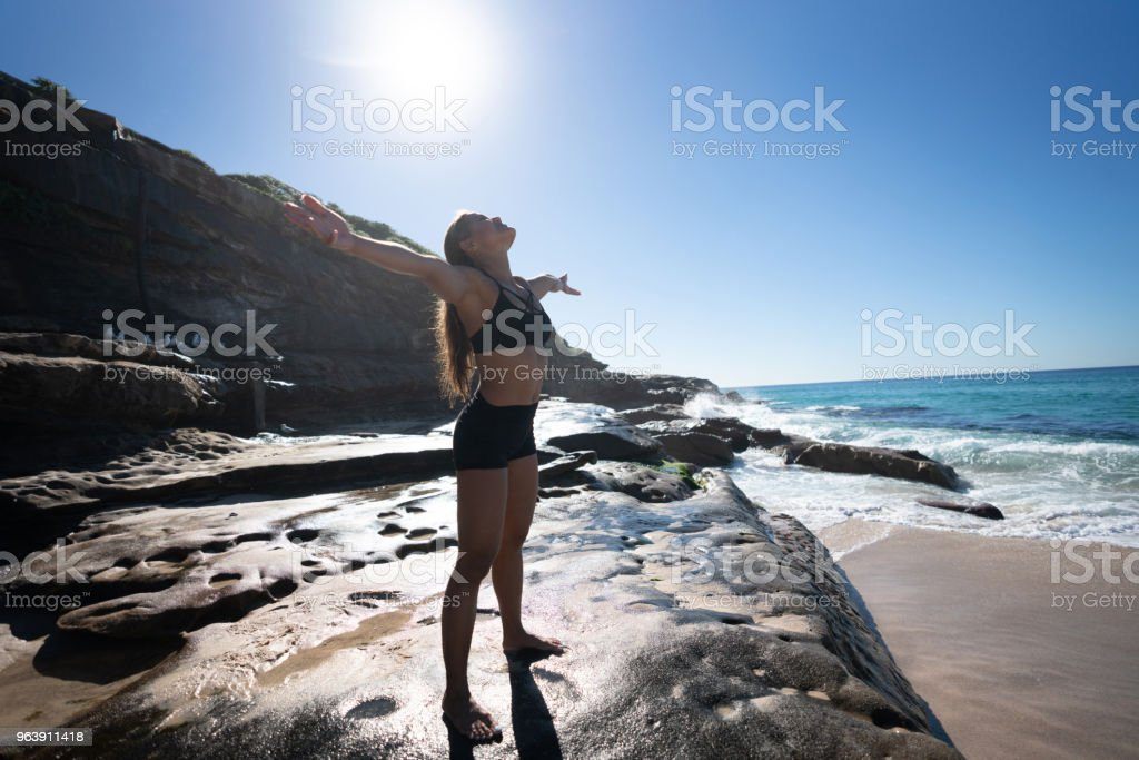 Woman doing stretching exercises at the beach - Royalty-free Adult Stock Photo